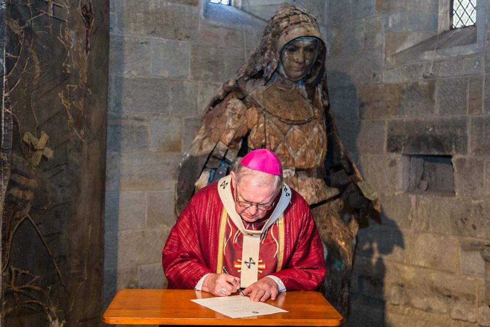 Archbishop Mark Coleridge signs the decree on Pentecost Sunday.